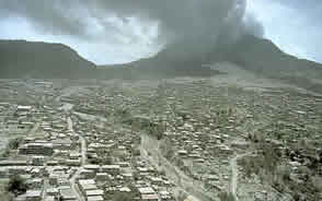 The Soufriere Hills volcano smokes over the destroyed town of Plmouth. MVO